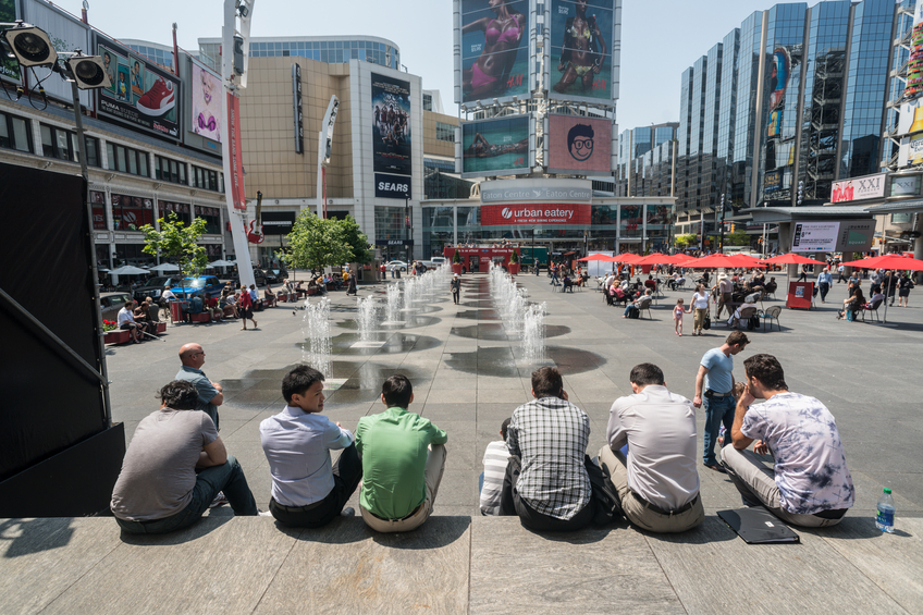 """Toronto, Canada - May 23, 2012: A group of friends sits on the stage area of Dundas Square on a hot May afternoon."""