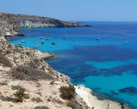 This is the magnificent island of rabbits, in Lampedusa. The water is crystal clear and the sand is white. The rocks are silhouetted against the blue sea and the sky is clear. The depths of this island are a paradise for divers because they are full of colorful fish.