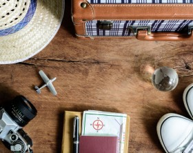 Outfit of traveler on wooden background, Vintage style