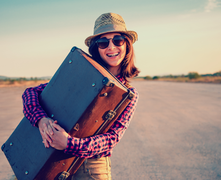 Happy woman traveler embraces a vintage suitcase on road. With a vintage retro instagram filter