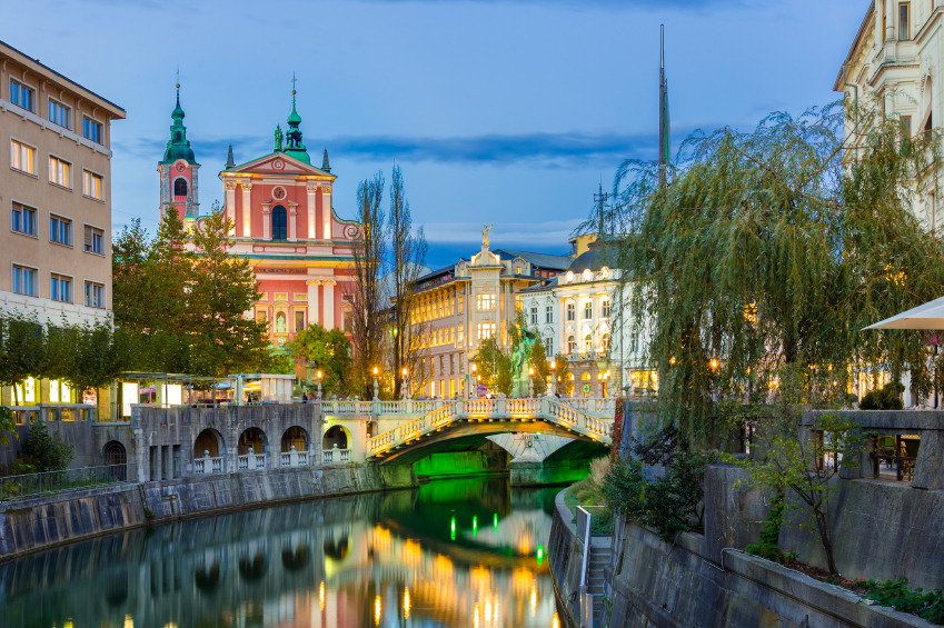 Romantic medieval Ljubljana's city center, capital of Slovenia, Europe. Night life on the banks of river Ljubljanica where many bars and restaurants take place. Franciscan Church in background