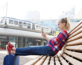 Smiling travel woman sitting outside with mobile phone