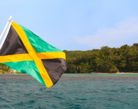 Jamaica flag waving sea beach sky. Selective focus on flag