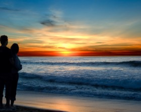 Young couple enjoying a sunset on the beach