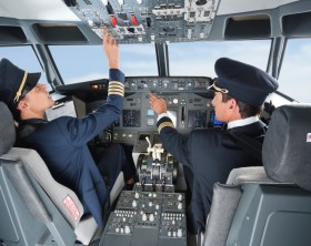 Pilot pushing button in airplane cockpit with co-pilot