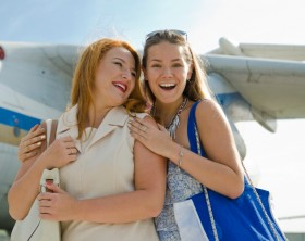 Two women mother and daughter met at the airport after a trip about aircraft