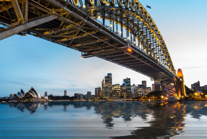 Dramatic widescreen panoramic image of the city of Sydney at sunset with bridge in foreground. Includes the Rocks, Bridge, Opera House, and a broad view of CBD and the water in the harbour