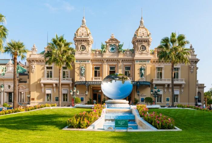 MONTE CARLO, MONACO - OCTOBER 3, 2014: Facade of Monte Carlo Casino in Monaco with Sky Mirror sculpture by Anish Kapoor in front