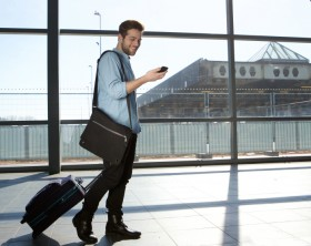 Full body portrait of a happy male traveler walking with bags and cellphone