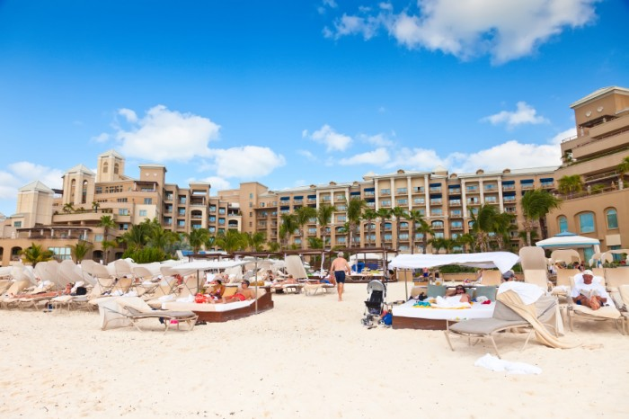 Grand Cayman, Cayman Islands - Mar. 8, 2013:  Tourists relax on beach of a luxury resort hotel.  Seven Mile Beach is the most populated area for hotels and resorts on the island.