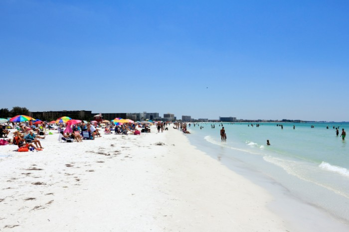 SIESTA KEY, FLORIDA - MAY 9, 2013: Many people relaxing on one of the top ten beaches in the United States, world renowned for its beauty and sand made of fine 99% pure white quartz that stays cool.