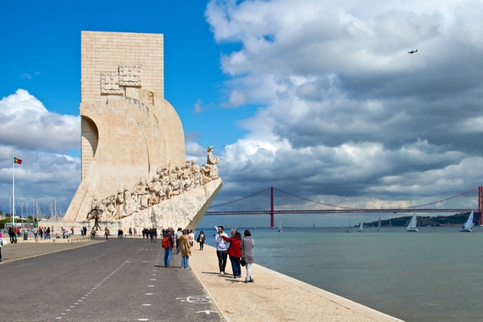Lisbon, Belem, Portugal, April 22th 2012: People walking close to the sea, where you can see the Monument to the Discoveries and the 25 April bridge in the back, while an airplane is landing in the Lisbon airport and boats navigate on the sea.