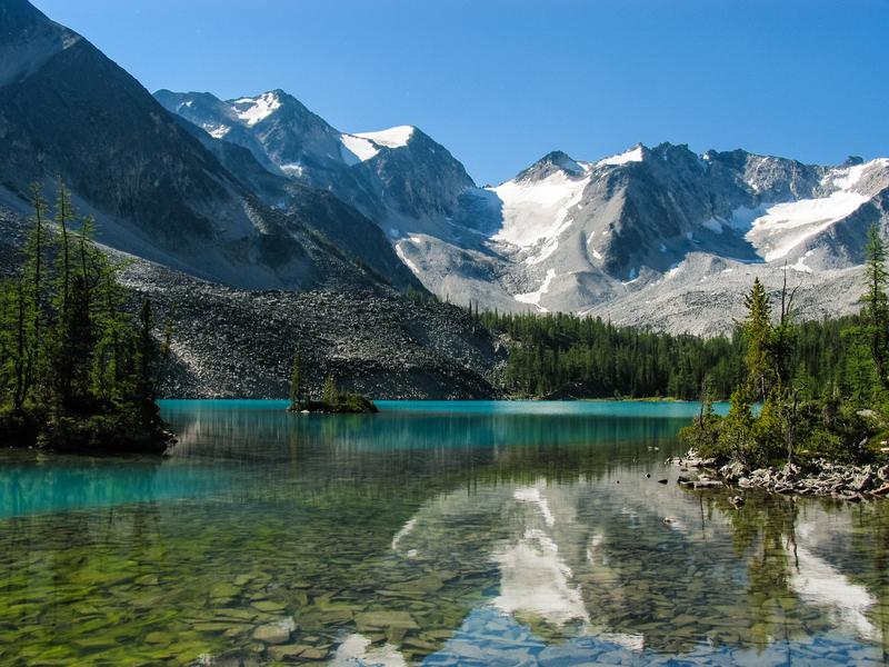 A calm alpine lake with a small island