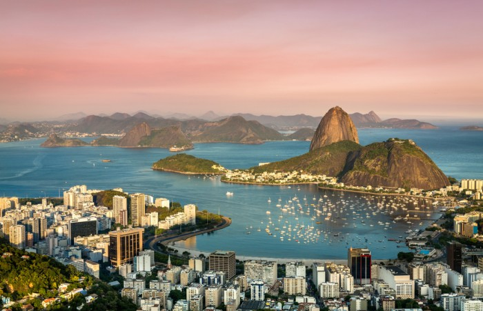 A photo of a sunset over the Botafogo Bay in Rio de Janeiro, Brazil.  The sky is made up of various shades of pink and purple due to the sunset.  The buildings of Rio de Janeiro's skyline are visible in the foreground of the photo around the blue water of the bay.  On the other shore are more buildings at the base of a mountain.  There are dozens of ships and sailboats in the bay between the shores.  More mountains and buildings are visible in the far distance on the horizon.