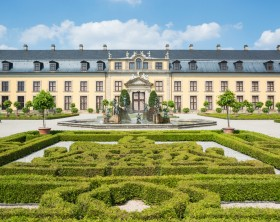Hannover, Germany - July 25, 2013: The facade of the Gallery in the Great Garden (Herrenhausen gardens) and ornamental boxwood. The Gallery is popular venue for classical concerts and winter shows.