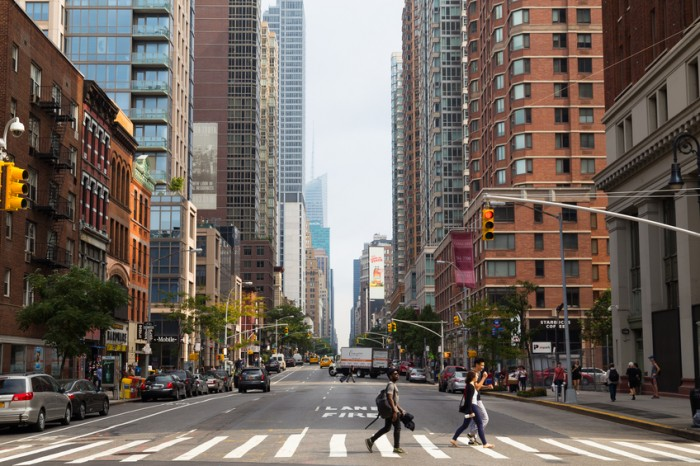 New York City, USA - August 31, 2014: A view up Sixth Avenue in New York City during the day. People and vehicles can be seen on the street