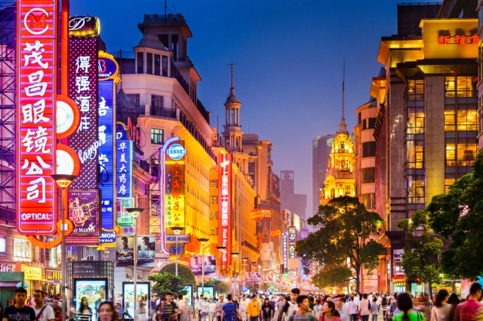 Shanghai, China - June 20, 2014: Crowds walk below neon signs on Nanjing Road. The street is the main shopping district of the city and one of the world's busiest shopping districts.