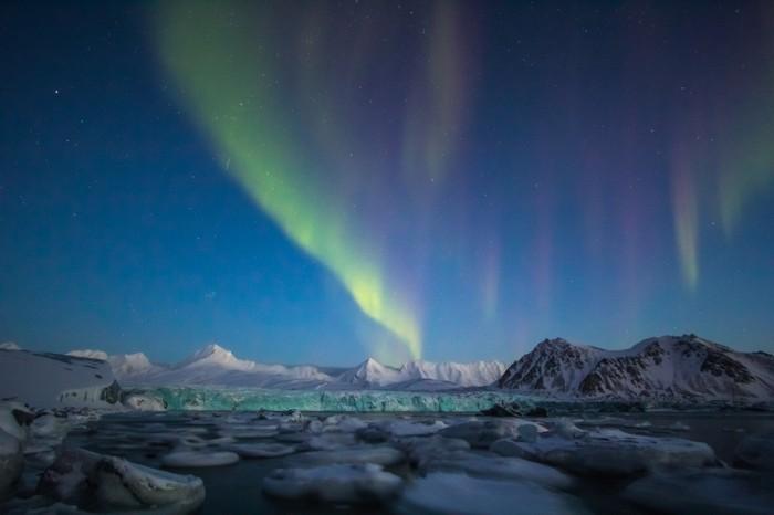Arctic winter in south Spitsbergen. Aurora borealis over arctic fiord.