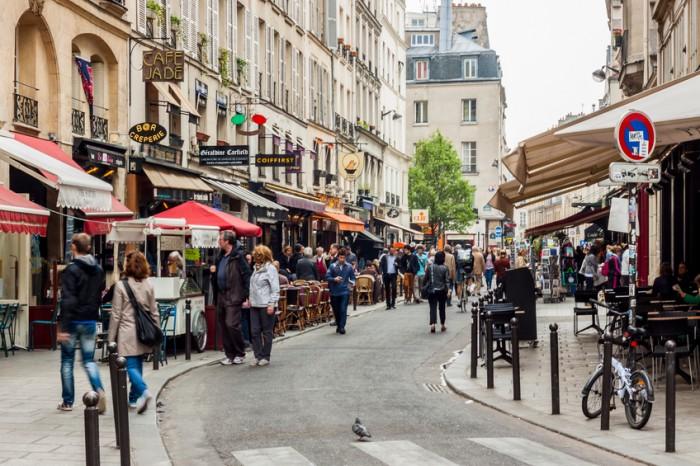 Paris, France - April 26, 2013: Tourists walk past a cafeteria and souvenir store. Paris is the most visited city in the world.