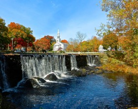 Quintessential New England (USA) scene. Local duck pond with waterfall, autumn colors, church, small town