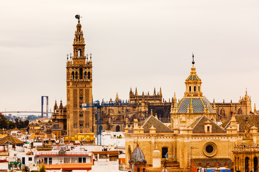 Giralda Spire Bell Tower Seville Cathedra, Cathedral of Saint Mary of the See Church of El Salvador Dome Seville Andalusia Spain.  Giralda is largest Gothic Cathedral in the World and burial Place of Christopher Columbus.