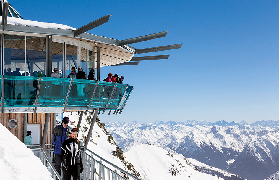 HOCHGURGL, AUSTRIA - MARCH 16 : Skiers enjoying the panoramic views across the Otztal Alps to the Dolomites from the Mountain Star viewpoint at Hochgurgl, Austria on 16th March 2013