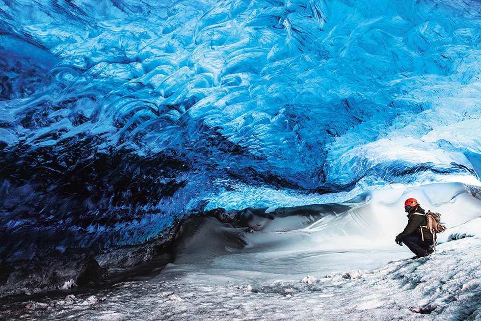 Man traveler enjoying exotic landmark, sitting in the ice cave, Skaftafell glacier, Vatnajokull National park, amazing nature of Iceland