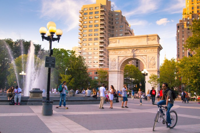 New York City, NY, USA - August 15, 2013: View of Washington Square Park in Manhattan with landmark arch and visitors present on a summer evening. Washington Square Park is a 9.75 acre park located in Greenwich Village and is a popular meeting spot.