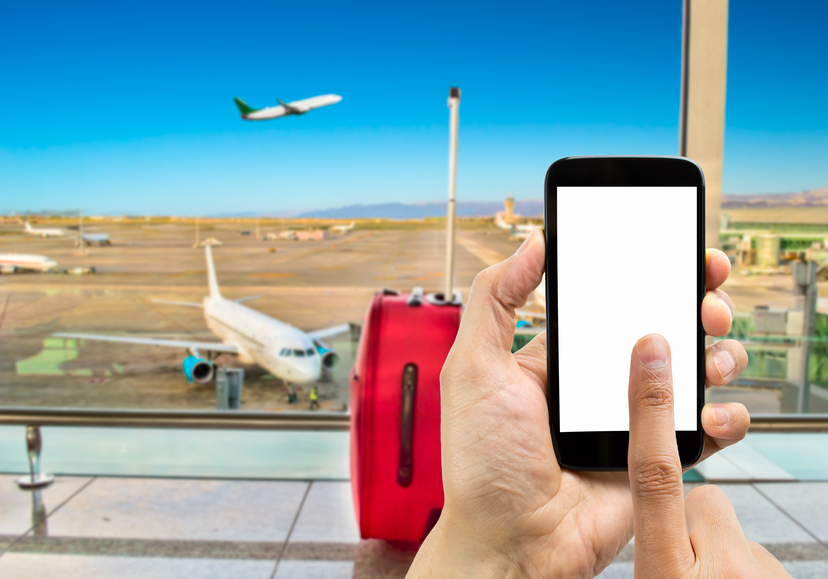 Hand holding smartphone with index finger touching the screen on the airport.