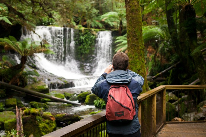 A tourist admiring the view at Horseshoe Falls, Mt Field National Park, Tasmania