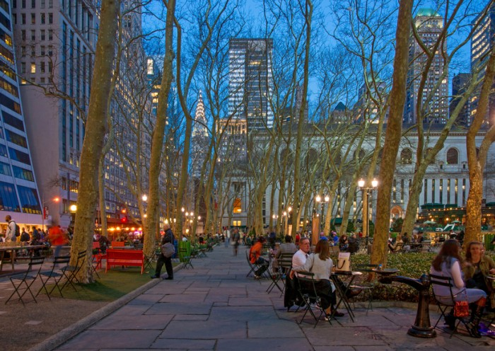 New York, U.S.A. - March 23, 2016: People Seating in Bryant Park Enjoying an early Spring Evening with trees, the Library and Chrysler Building in the Background