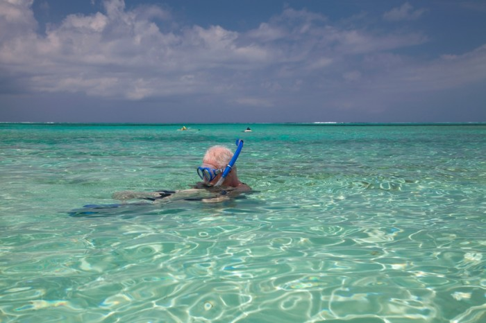 """Older middle-aged man and two older children snorkeling off-shore in Grace Bay, Turks and Caicos Islands."""