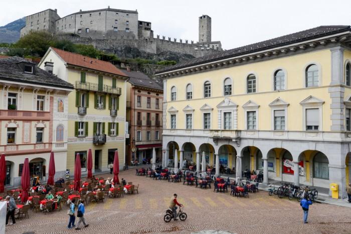 Bellinzona, Switzerland - 15 October 2014: People walking and sitting on restaurants at Collegiata square of Bellinzona on Switzerland