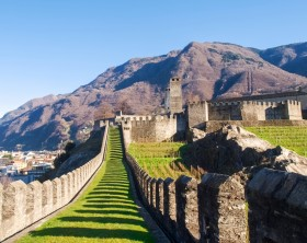 Bellinzona, Switzerland - december 20, 2014: along the pedestrian path of the castles of Castelgrande, Montebello, Sasso Corbaro. The Wall of Castelgrande is illuminated from afternoon light.