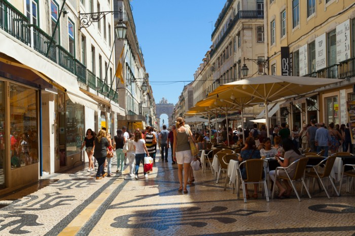 Lisbon, Portugal - May 30, 2015: Street scene of Rua Augusta in the Baixa district in Lisbon in Portugal with tourists and outdoor restaurants. You can see the Augusto Arch at the end of the street.