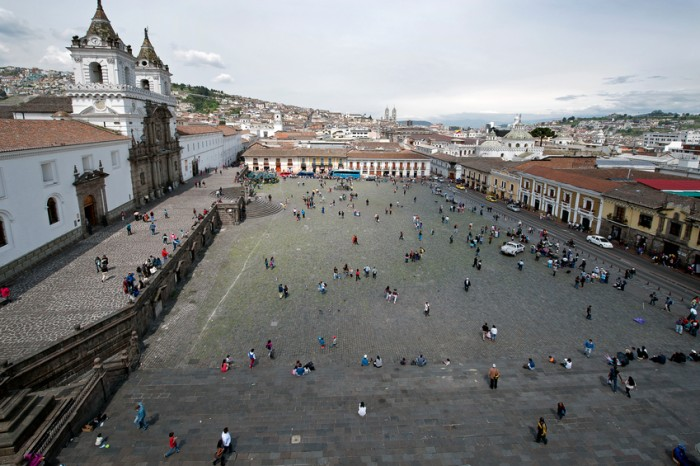 Quito, Ecuador - November 15, 2014: The huge Plaza de San Francisco is dominated by the Basilica San Francisco, a massive religious complex, the largest in Latin America. , seen from above,people gather in the square in the early morning with old Quito in the background