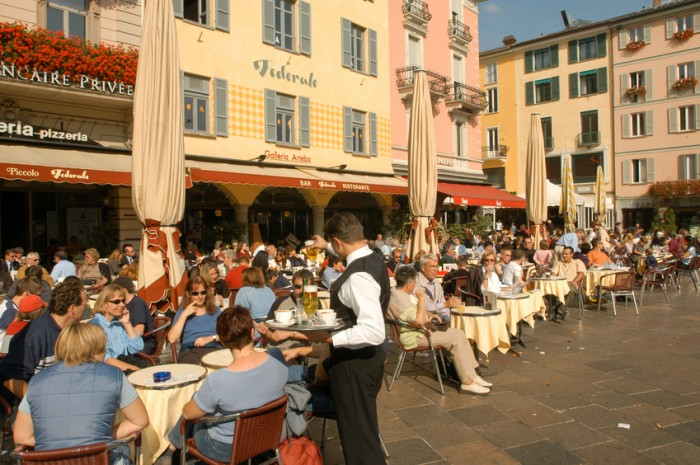 Lugano, Switzerland - 7 October 2002: People eating and drinking at restaurants of the central square of Lugano on the italian part of Switzerland