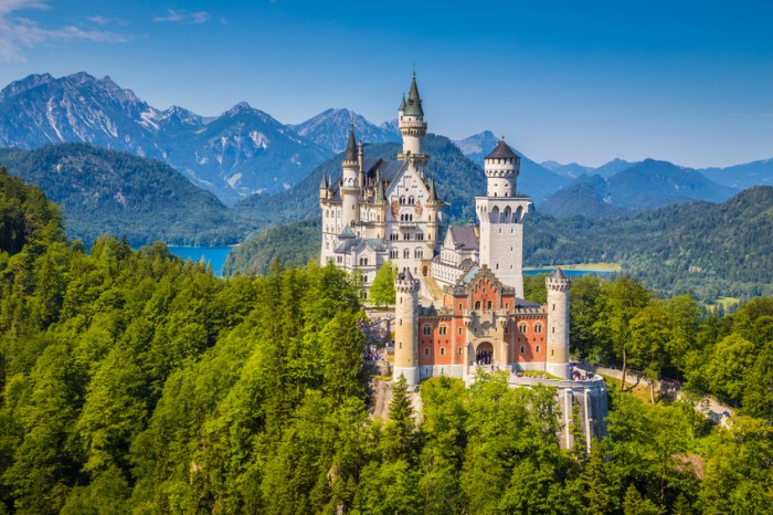 Fussen, Germany - August 7, 2015: Beautiful view of world-famous Neuschwanstein Castle, the nineteenth-century Romanesque Revival palace built for King Ludwig II on a rugged cliff, with scenic mountain landscape near Fussen, southwest Bavaria, Germany.