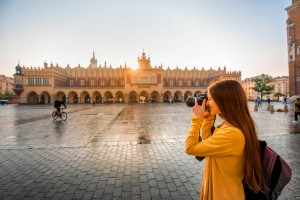 Young female tourist with camera and backpack photographing Cloth Hall in the old city center of Krakow