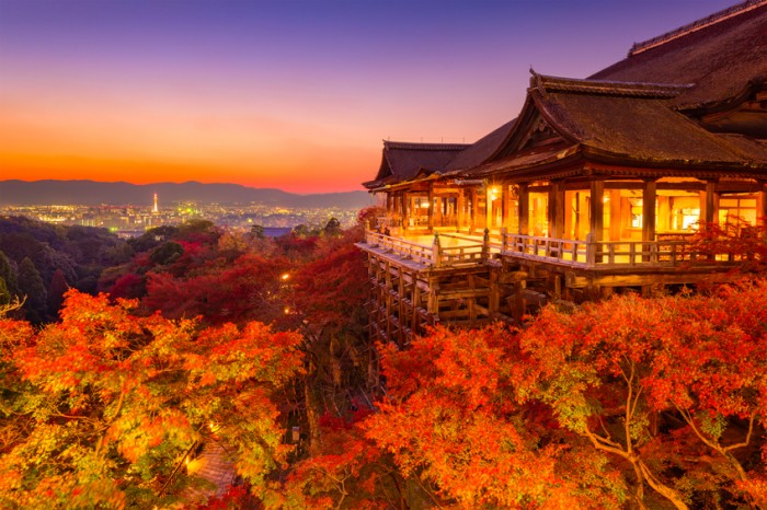 Kyoto, Japan - November 30, 2015: Tourists stand on the stage of Kiyomizudera Temple during the autumn season at dusk. The temple was founded in the 700's and the present stage structure dates from 1633.