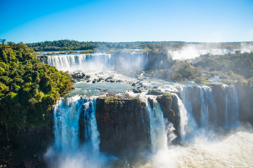Iguazu Falls is located where the Iguazu River tumbles over the edge of the Paraná Plateau, 23 kilometres (14 mi) upriver from the Iguazu's confluence with the Paraná River.