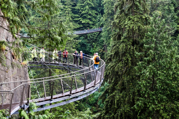 Vancouver, ?anada - June 29, 2011: Visitors explore the Capilano Cliff Walk through rainforest vegetation. The cantilevered and suspended walkways jut out from the granite cliff face 230 metres above the Capilano River.