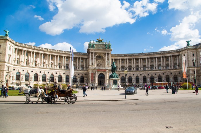 Vienna, Austria - April 3, 2015: Hofburg palace and square view, people walking and fiaker with white horses  in Vienna, Austria