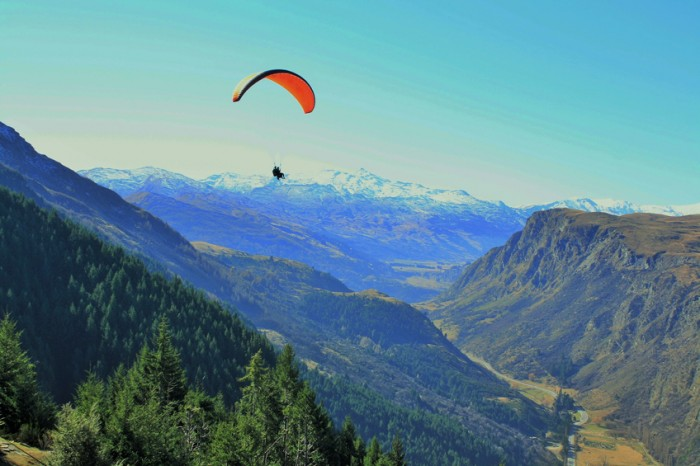 Tandem paragliding from the top of the mountain above Queenstown, New Zealand.  Uniterupted view of mountains, Gorge Road and stunning scenery.  Taken on a clear winters day.