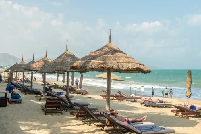 Nha Trang, Vietnam - Mar 22, 2014: European tourists take rest on the beach of Nha trang in Mar 22, 2014. Nha trang beach are the most beautiful beach in Vietnam