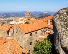 background views cityscape Monsanto village with houses made of stone among the boulders and roofs and red brick, the town hall with a clock and a huge boulder