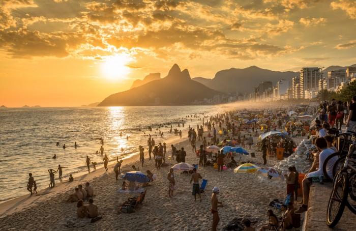 Rio De Janeiro, Brazil - February 10, 2016: People watching sunset on iconic Ipanema Beach in Rio de Janeiro. Rio will host 2016 Summer Olympic Games.