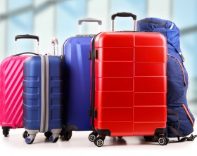 Plastic travel suitcases in the airport hall.