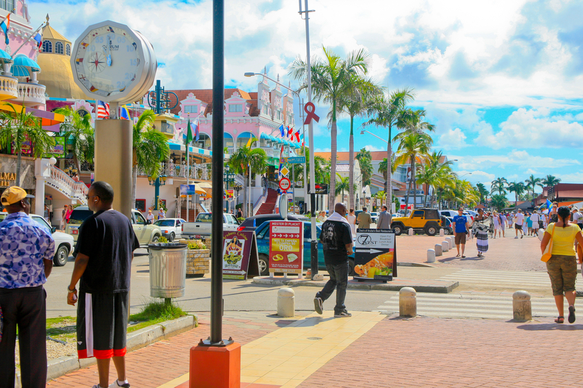Oranjestad, Aruba, December 1, 2011- Main Street with tourists walking up and down the street. Stores and the Royal Plaza are along the left side.