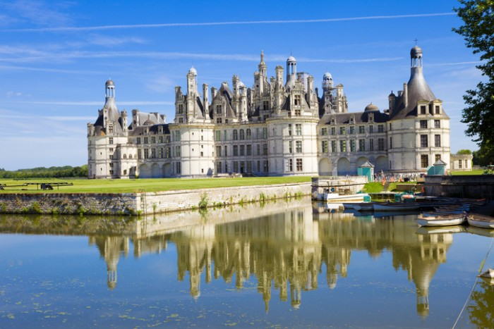 """""""Chambord, France - July 31, 2009: Great panoramic of Chambord Chateau reflected in the canal in a summer day with blue sky. There are some unrecognizable people in the balconies"""""""